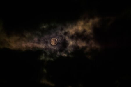 lonesome: Photo of night cloudy sky and moon, defocused background. Not an illustration.