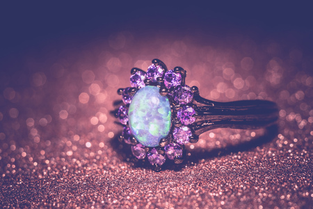 ring of fire: Fashion ring decorated with blue fire opal stones, filtered background.