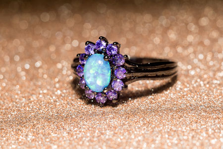 Fashion ring decorated with blue fire opal stones. Stock Photo