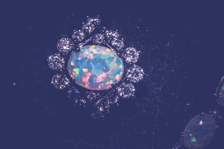 ring of fire: Fashion ring decorated with white fire opal stones, filtered background.