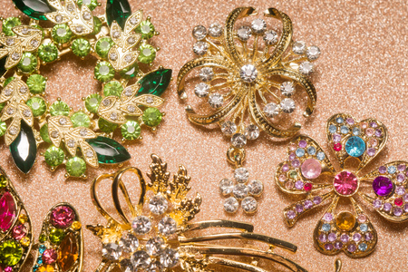 Collection of different golden brooches decorated with rhinestones, fashion jewellery. Reklamní fotografie
