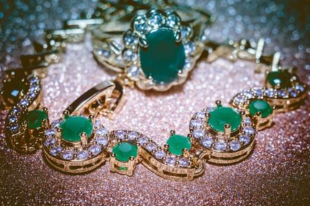 green gemstone: Elegant female jewelry golden ring with precious green gem, emerald, filtered background.