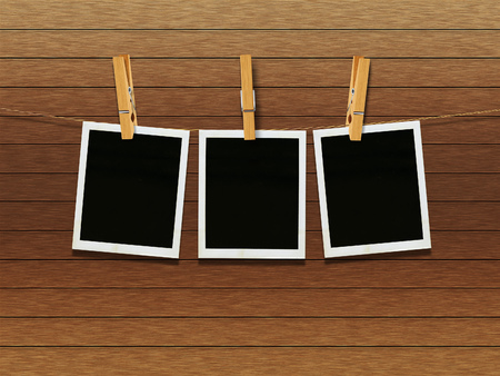 old photograph: Old photo film blanks hanging on a rope held by clothespins over wooden background.
