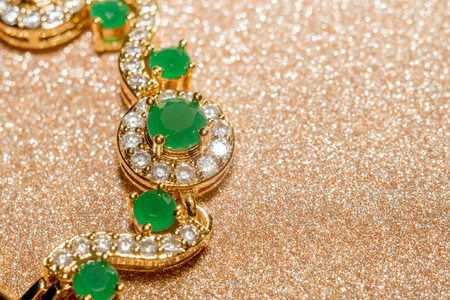 green gemstone: Elegant female jewelry golden bracelet with precious green gem, emerald.