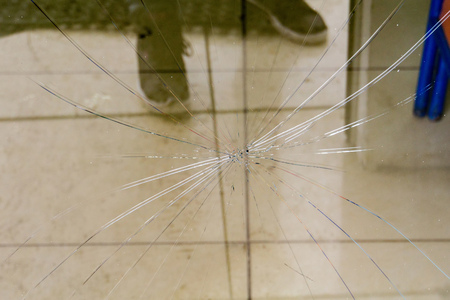 Damaged glass with cracks as abstract grunge background. Stock Photo