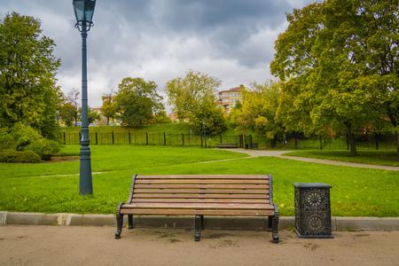 도시 공원에서 갈색 외로운 나무 벤치입니다.