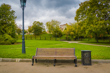 Brown lonely wooden bench in the city park. Banque d'images