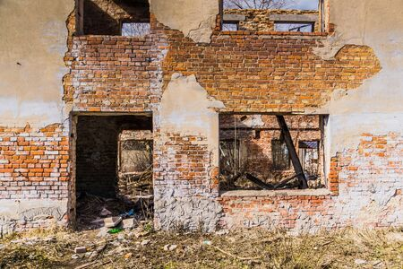 Old crumbling brick house, windows in ruined abandoned building background.