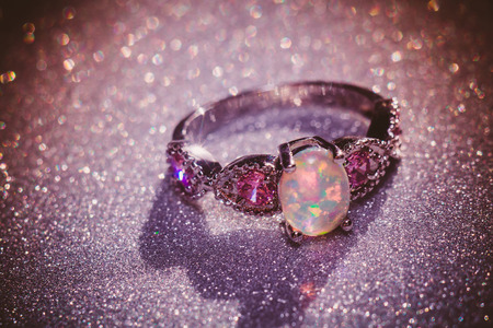 Fashion ring decorated with white fire opal stones, filtered background.
