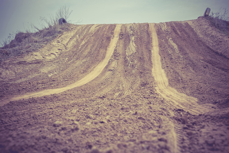 Trail of treads on a sandy quarry retro background.