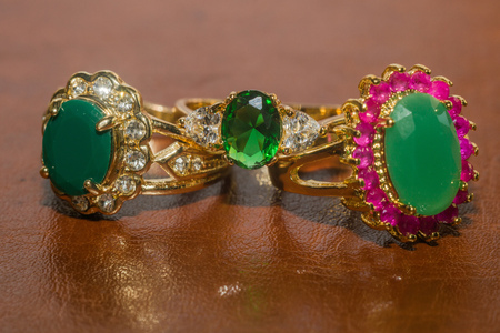 Elegant female jewelry golden ring with precious green gem, emerald. Reklamní fotografie - 84290239