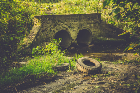 Large old concrete drain pipe, culvert in the grass, filtered background. Stock Photo