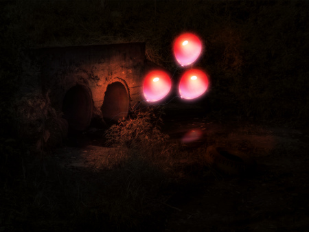 Glowing red balloon comes out from old concrete culvert in the night.