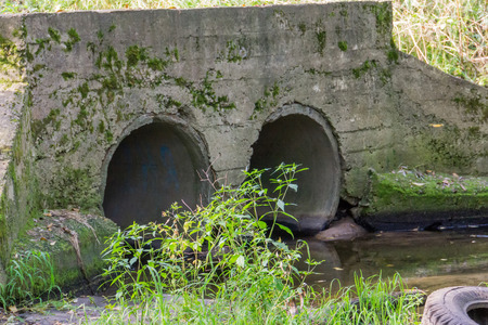 Large old concrete drain pipe, culvert in the grass. Stock Photo