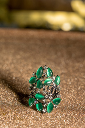 Silver ring decorated with zircons and green tiger or cat eye stone imitation. Stock Photo
