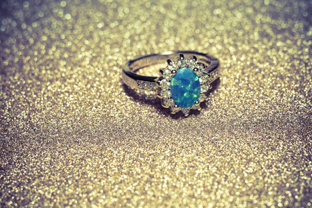 Fashion golden ring decorated with blue fire opal stones.