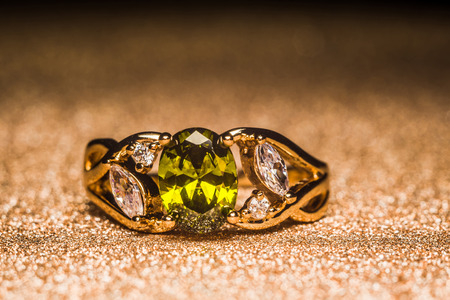 Precious golden ring decorated with green stone, zirconia.
