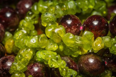 Dark red beads of garnet and olive green peridot gravel, natural stone close up. Фото со стока