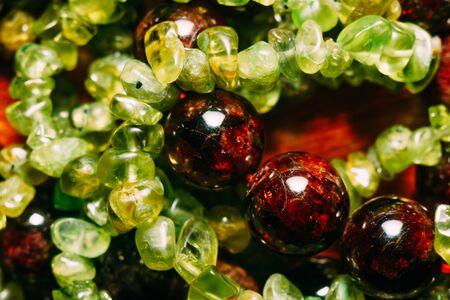 Dark red beads of garnet and olive green peridot gravel, natural stone close up. Stockfoto