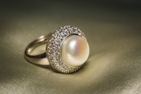 Luxury silver ring decorated with freshwater pearl of white color and diamonds. Imagens