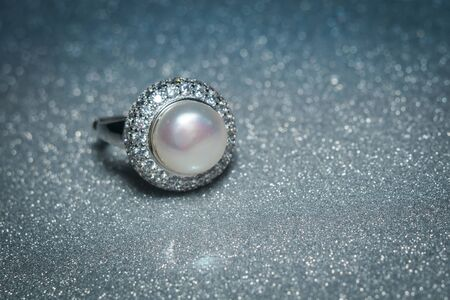 Luxury silver ring decorated with freshwater pearl of white color and diamonds. Stock Photo