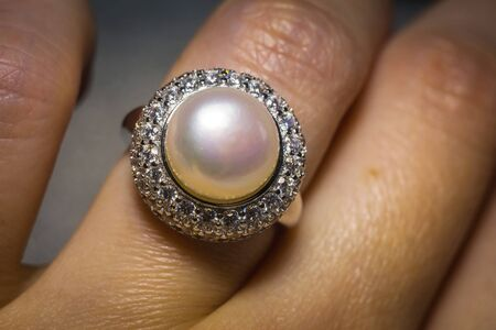 Luxury silver ring decorated with freshwater pearl of white color and diamonds. 写真素材