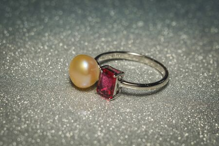 Luxury silver ring with natural freshwater pearl of yellow color, macro.