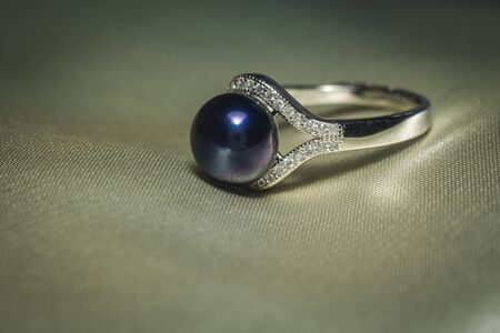 Luxury silver ring with natural freshwater pearl of black color, macro. Stock Photo