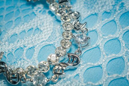 Fashion silver bracelet with white cubic zirconia on blue lace background. Stock Photo