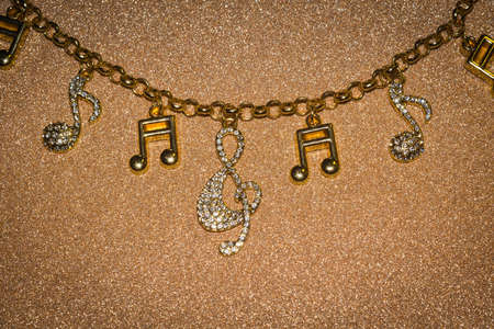 Fashion bracelet with decorative gold charms in a shape of a music note background. Banque d'images