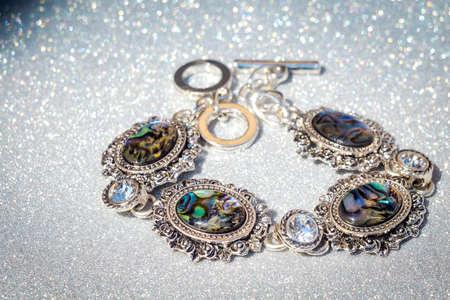 Fashion retro silver bracelet decorated with dark rainbow abalone shell on glitter background.