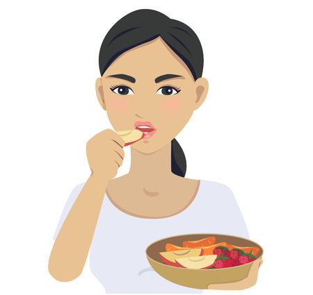 Frauen essen einen Apfel und hält eine Platte von Früchten.