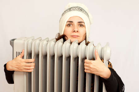 calorifer: Freezing young woman near a heater