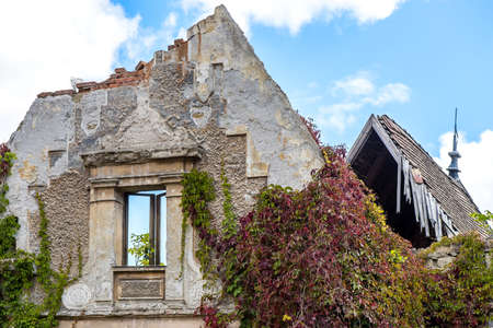 damaged roof: Old abandoned house with vegetation and clouds in background