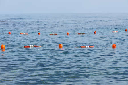Orange buoys at safe swimming zone in the sea Stock Photo