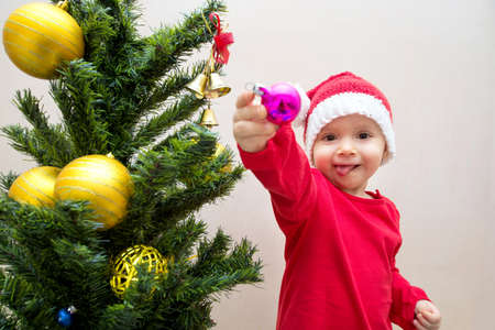Baby near the christmas tree holding a christmas ball