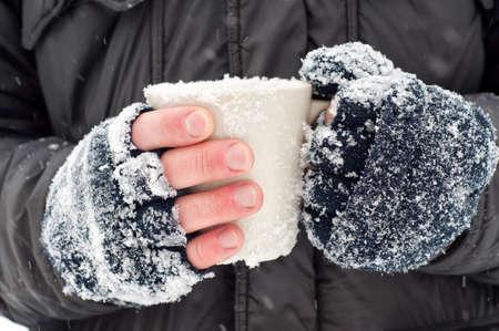 Frozen hands of a man holding a mug Stock Photo