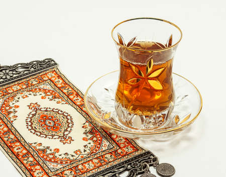 crystalline gold: Turkish tea with traditional turkish carpet on white background