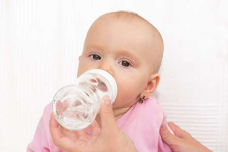 Baby eating from milk bottle, white background, isolated