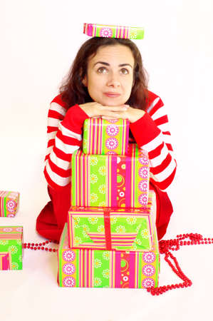 Young woman dressed in red with presents. Studio shot
