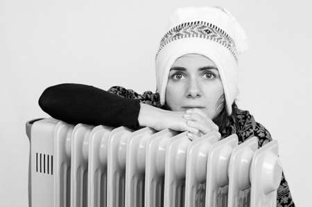 Young woman freezing near a heater. Black and white shot