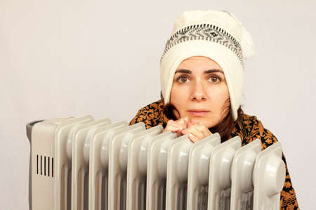 Young woman freezing near the heater studio shot