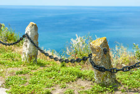 Old fence with chain near the sea