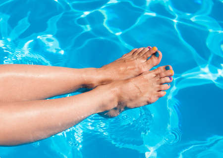 Girls legs at the pool. Vacation fun Stock Photo