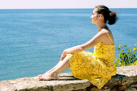 欄干の上に座って、海を眺めの美しい若い女性 写真素材