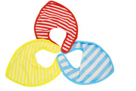 Baberos de bebé aislados rojo, amarillo y azul Foto de archivo - 82968566
