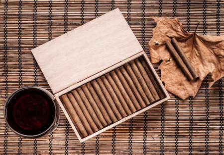 Cigarillos, wine and an old leaf still life Stock Photo