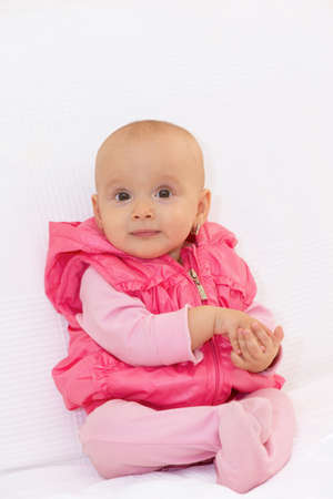 Baby girl with pink gilet on the white background