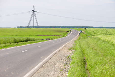 Road in a rural area with green wheat field