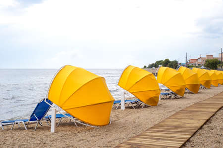 Wooden walkway, umbrellas and sunbeds on the beach Stock Photo